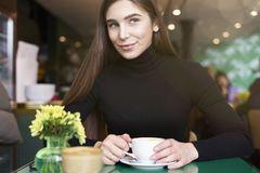 Young woman in black jersey look to camera, drink coffee and having rest in cafe near window. Young woman in black jersey look to camera, drink coffee and Stock Image