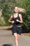 Young woman in black jogs outside. Stock Photos
