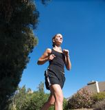 Young woman in black jogs outside. On a sunny day Royalty Free Stock Photography