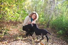 Young woman with black labrador retriever puppy Stock Image