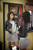 Young woman in black leather jacket and gray short tutu skirt looking into a large mirror. Beautiful curly dark hair girl posing Royalty Free Stock Photography
