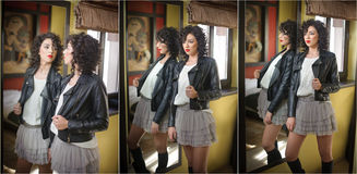 Young woman in black leather jacket and gray short tutu skirt looking into a large mirror. Beautiful curly dark hair girl posing Stock Photos