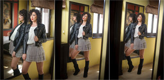 Young woman in black leather jacket and gray short tutu skirt looking into a large mirror. Beautiful curly dark hair girl posing Royalty Free Stock Images