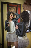 Young woman in black leather jacket and gray short tutu skirt looking into a large mirror. Beautiful curly dark hair girl posing Stock Image