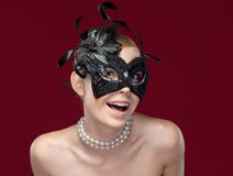 Young woman with black masquerade mask with feathers Royalty Free Stock Image