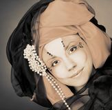 Young woman in black and orange turban Stock Images