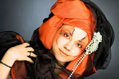 Young woman in black and orange turban Royalty Free Stock Images