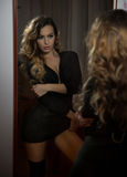 Young woman in black outfit looking into large wall mirror. Beautiful curly fair hair girl posing in front of mirror royalty free stock photography