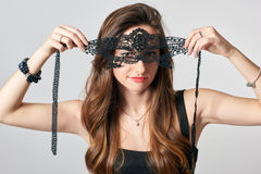 Young woman in black party mask Stock Images
