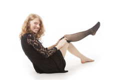 Young woman in black putting on stocking Royalty Free Stock Photography