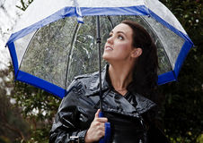 Young woman in black raincoat. Young woman in shiny black raincoat with umbrella ready for wet winter weather Royalty Free Stock Images