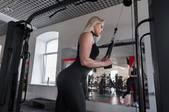 Young woman in black sportswear is doing strength exercises for hands in modern gym. Girl goes in for sports. Healthy lifestyle. Side view royalty free stock images