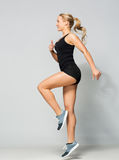 Young woman in black sportswear jumping Stock Photo