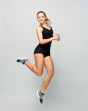 Young woman in black sportswear jumping Stock Photos