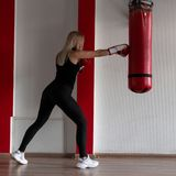 Young woman in black sportswear in stylish sneakers in red boxing gloves beats a punching bag in a modern gym. Girl in training. Indoors stock photography