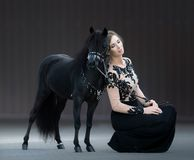 Young woman with black stallion. American Miniature Horse. Young woman with black stallion on dark background. American Miniature Horse Stock Images