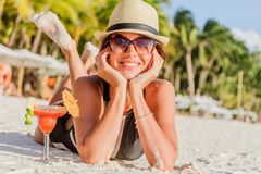 Young woman in black swimsuit with cocktail on the beach in trop Royalty Free Stock Image