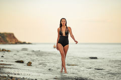 Young woman in black swimsuit goes on sand beach by the sea. Royalty Free Stock Images