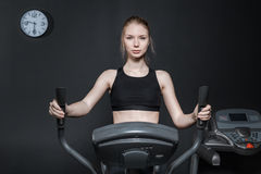 Young woman in black tank top is doing exercises for the leg muscles on the exerciser. The woman is engaged in against the black wall on which hang the clock Stock Photo