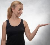 Young woman in black tank top with open hand royalty free stock image