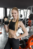Young woman in black top doing exercises with dumbbells at the gym. Stock Photography