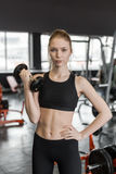 Young woman in black top doing exercises with dumbbells at the gym. Royalty Free Stock Photography