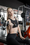 Young woman in black top doing exercises with dumbbells at the gym. Royalty Free Stock Image