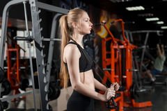 Young woman in black top standing with a skipping rope in his hands in the gym. Royalty Free Stock Image