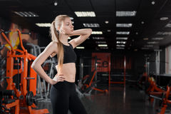 Young woman in black top standing with a skipping rope in his hands in the gym. Royalty Free Stock Photography
