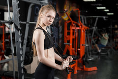 Young woman in black top standing with a skipping rope in his hands in the gym. Stock Photo