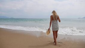Young woman in black and white dresses walking alone on a tropical beach and watching the storm on the sea. Travel. Young woman in black and white dresses stock footage