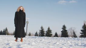 Young woman in black winter coat standing in front of blue sky tracking camera movement. Young woman in black winter coat standing in front of blue sky stock video