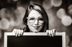 Young woman with blackboard and glasses royalty free stock photo