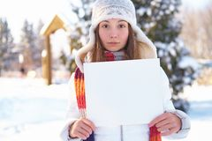 Young woman with blank banner outdoors. Winter. Royalty Free Stock Photography