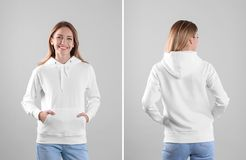 Young woman in blank hoodie sweater on light background, front and back views. Mock up for desing royalty free stock images