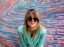 Young woman in Blazer of 90s style and sunglasses. Stay near striped and colored background royalty free stock image