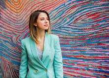 Young woman in Blazer of 90s style. Stay near striped and colored background stock images