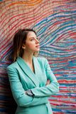 Young woman in Blazer of 90s style. Stay near striped and colored background stock image