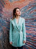 Young woman in Blazer of 90s style. Stay near striped and colored background stock photography