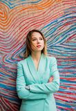 Young woman in Blazer of 90s style. Stay near striped and colored background royalty free stock images