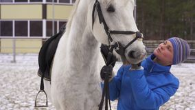 A young woman in a blazer and sports hat is riding a white horse in a fenced area. Cloudy winter day stock video