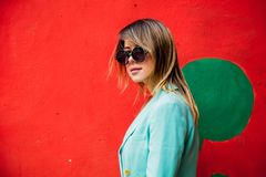 Young woman in Blazert of 90s style and sunglasses. Young woman in Blazer of 90s style and sunglasses in red background stock images