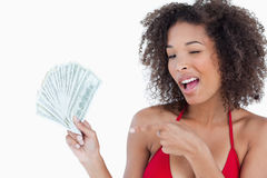 Young woman blinking an eye while holding a fan of notes Royalty Free Stock Images