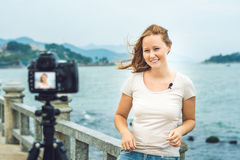 A young woman blogger leads her video blog in front of a camera by the sea. Blogger concept Royalty Free Stock Image