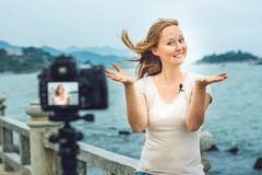 A young woman blogger leads her video blog in front of a camera by the sea. Blogger concept Stock Photos