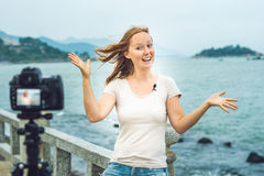 A young woman blogger leads her video blog in front of a camera by the sea. Blogger concept Stock Images
