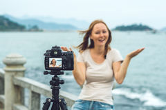 A young woman blogger leads her video blog in front of a camera by the sea. Blogger concept Royalty Free Stock Photo