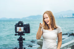 A young woman blogger leads her video blog in front of a camera by the sea. Blogger concept Royalty Free Stock Photos