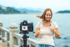 A young woman blogger leads her video blog in front of a camera by the sea. Blogger concept Royalty Free Stock Photography