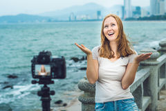 A young woman blogger leads her video blog in front of a camera by the sea. Blogger concept Stock Image